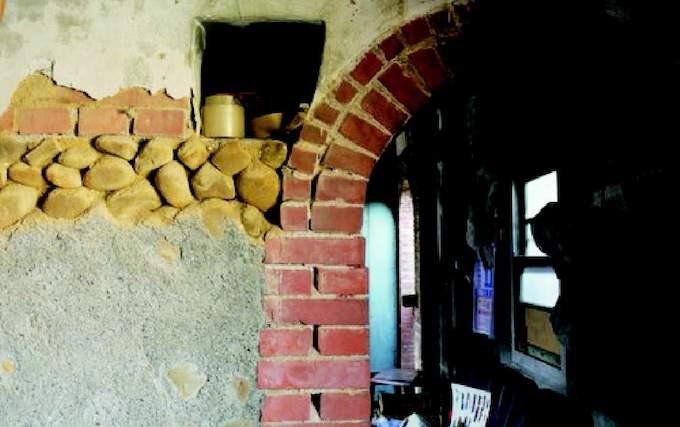 屋內斑駁的牆,可看見建築材料:磚頭、石頭、石灰拌砂土。水泥部分是天虎叔自己砌抹上的。